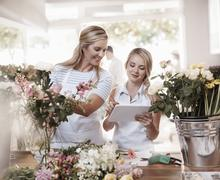 Florists with digital tablet arranging bouquet in flower shop - stock photo