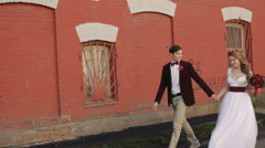 Newlyweds Walking Along Brick Red Wall. Wide Shot Stock Footage