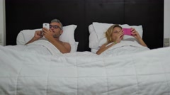 happy couple having fun using smartphone on bed - stock footage