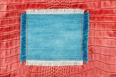 Frame made of denim with a fringe is on the red crocodile skin - stock photo