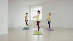 Yoga class doing  pose together on exercise mats at the gym Stock Footage