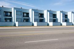 Row of identical apartments along street - stock photo