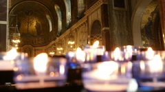 Votive candles in a catholic cathedral. - stock footage