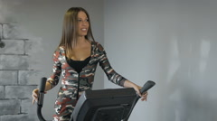 Beautiful young lady using the elliptical trainer in a gym in a positive mood Stock Footage
