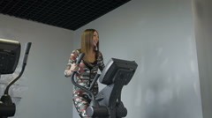 Stock Video Footage of Beautiful young lady using the elliptical trainer in a gym in a positive mood