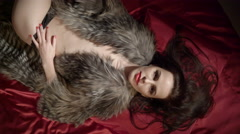 Sexy brunette woman covered with fur jacket lying on dark red silk satin bed Stock Footage