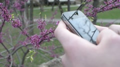 Mobile Cell Phone in the Hands of a Man - chating wrighting sms - in a city park Stock Footage