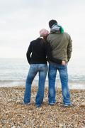 Couple on beach, looking out to sea - stock photo