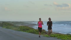 Healthy couple jogging along ocean road Stock Footage