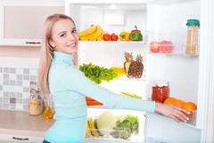 Young blonde at home near fridge - stock photo