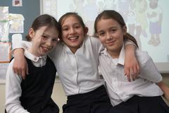 Girls smiling at camera, in classroom - stock photo