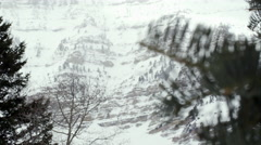 View of snow  covered cliffs on mountain past pine tree branches. Stock Footage