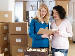 Two women with boxes in kitchen Stock Photos