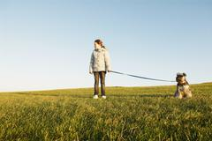 Girl with dog on lead, expanse of sky Stock Photos