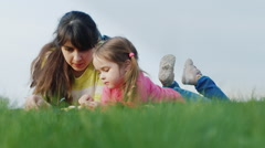 A woman with a girl of 3 years lying on green grass, chatting Stock Footage