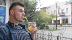 Man drinks orange juice from a glass - cafe on the terrace of old town Stock Footage