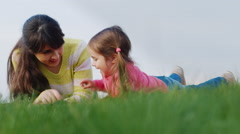 Mother and daughter playing on the green grass Stock Footage