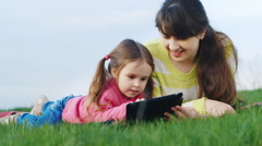 Mother and daughter enjoying a picnic tablet Stock Footage