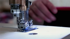 Worker sewing fabric with sewing machine Stock Footage