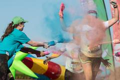 Volunteers Douse Runners With Colored Corn Starch At Color Run Stock Photos