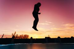 Silhouette Of Beautiful Plus Size Young Woman Girl Jumping On Tr - stock photo