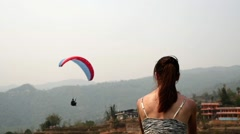 Girl looks at the flying paraglider Stock Footage