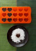 Chocolate heart-shaped candy on a brown plate with sugar powder - stock photo