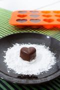 Chocolate heart-shaped candy on a brown plate with sugar powder Stock Photos