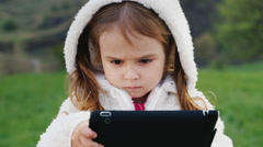 Very serious girl 3 years old with a tablet Stock Footage