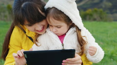 Mother and daughter 3 years old playing on a tablet outdoors Stock Footage