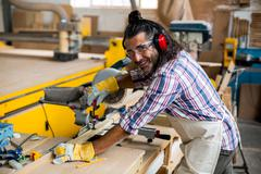 Carpenter cutting wooden plank with electric saw Stock Photos