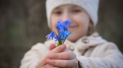 Girl holding a blue snowdrops - stock footage