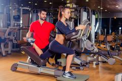 Personal trainer helping woman working with lunges, leg coaching Stock Photos