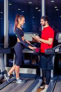 Personal trainer helping woman working with treadmill Stock Photos