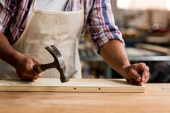 Carpenter using hammer on wood Kuvituskuvat