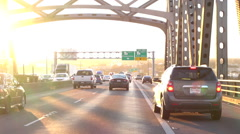 Driving over the busy traffic bridge full of cars and trucks at golden sunset - stock footage