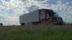 Big freight semi trucks speeding and passing by on highway across the country - stock footage