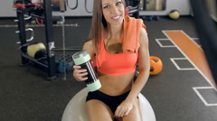Fitness young woman with towel and shaker smiling, she is sitting on pilates Stock Footage