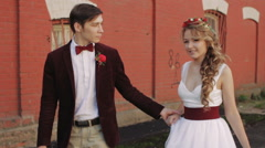 Bride and Groom Walking Along a Brick Red Wall Stock Footage