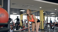 Woman working out at a gym with exercise equipment Stock Footage