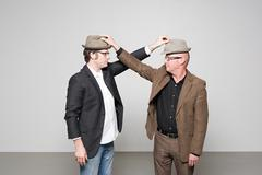 Men holding hats Stock Photos