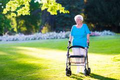Senior handicapped lady with a walker in a park - stock photo