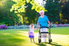 Grandmother with walker and little girl in a park Stock Photos