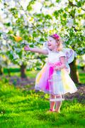 Little girl in fairy costume feeding a bird Stock Photos