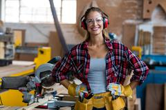 Portrait of female carpenter standing with hand on hip Stock Photos