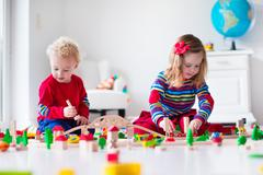 Children playing with toy railroad and train - stock photo