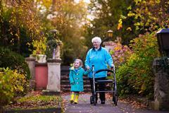 Senior lady with walker enjoying family visit - stock photo