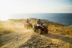 People riding all terrain vehicles - stock photo