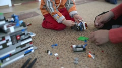 Children playing with Lego on the floor in the room - stock footage