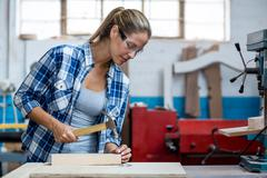 Female carpenter holding a hammer to drive nail into a wooden plank Stock Photos